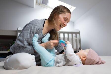 Joyful mom entertaining baby with rattle toy, having fun with daughter in bedroom. Mother and little child staying at home. Child care or isolation concept Foto de archivo