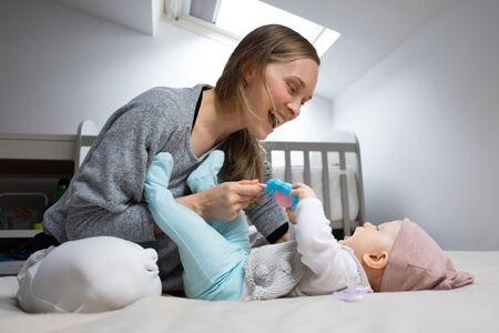 Fröhliche Mutter, die Baby mit Rasselspielzeug unterhält und Spaß mit Tochter im Schlafzimmer hat. Mutter und kleines Kind bleiben zu Hause. Kinderbetreuung oder Isolationskonzept Standard-Bild
