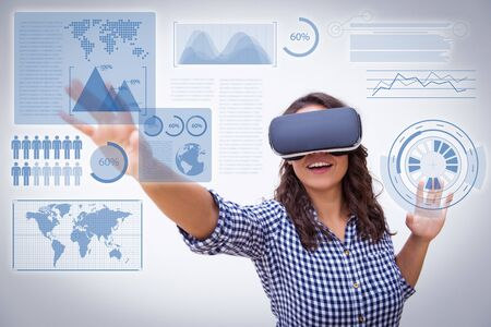 Positive female user in VR goggles touching virtual worldwide business charts. Young woman in virtual reality headset standing isolated over white background. Augmented reality concept