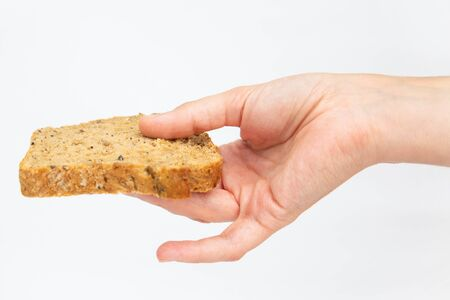 Woman hand holding one slice of cereal bread by fingers. Sliced homemade loaf with oats and seeds isolated on white background. Studio shot. Top view. Home culinary and baking concept