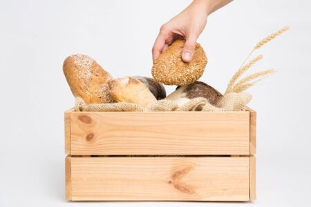 Closeup of holding loaf at wooden crate with freshly baked bread and wheat ears. Side view. Isolated object on white background. Baking or traditional bread concept Фото со стока