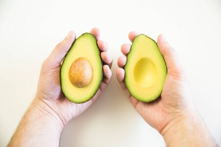 Two halves of avocado with core in human hands. Closeup shot. Isolated objects on white background. Fresh food or healthy diet concept