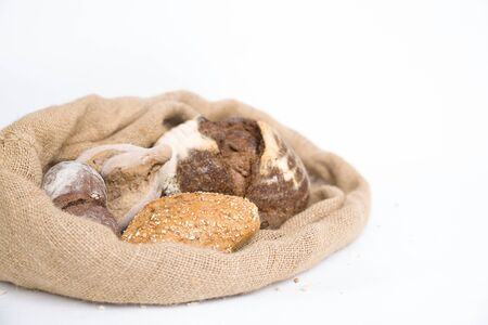 Fresh rye and wheat buns in rustic burlap sack. Closeup shot. Isolated object on white background. Bakery or freshly baked bread concept