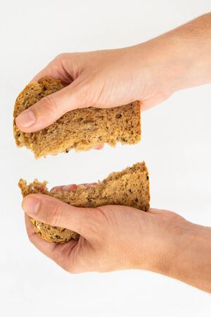 Hands tearing slice of cereal bread on two pieces. Delicious rye loaf and pastry for sandwich isolated on white background. Studio shot. Top view. Homemade bakery and nutrition concept