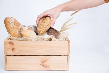 Person taking French loaf from rustic wooden box with rye and wheat bread and ears. Side view. Isolated object on white background. Baking or traditional bread concept
