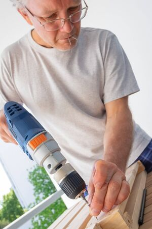 Grey haired man using drill driver for assembling furniture at home, doing carpentry work on balcony. Vertical shot. Male household chores concept Stok Fotoğraf