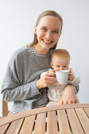 Happy new mom and cute baby daughter holding mug of tea together. Front view portrait. Child care and tea break concept