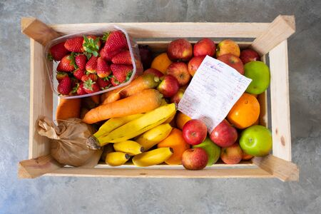 Wooden box full of fresh vegetables and paper with product list on floor. Top view. Local fruits or organic food delivery concept Stockfoto