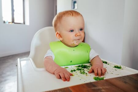 Portrait of dirty baby girl sitting on highchair at dining table. Little child starting eating by herself. Led weaning and self-feeding concept