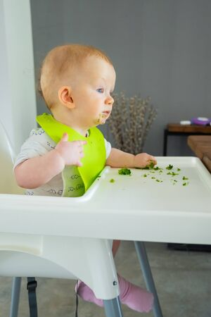 Sweet baby making mess while eating broccoli vegs. Little child wearing plastic bib, sitting in highchair. First solid food or child care at home concept
