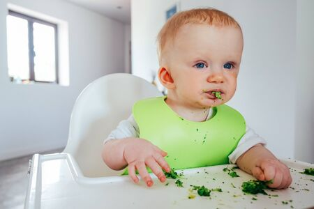 Funny baby girl eating soft cooked vegetables by herself. Little child sitting on highchair and having meal. Led weaning and self-feeding concept
