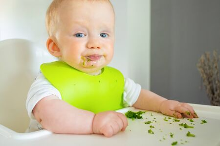 Naughty baby trying to eat broccoli vegs, posing with food spots on face, making messy on tray. Little child wearing plastic bib, sitting in highchair. First solid food or child care at home concept