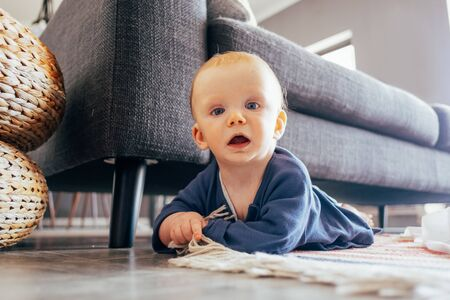 Funny baby girl lying on rag at couch in living room. Little child crawling at home. Infancy concept