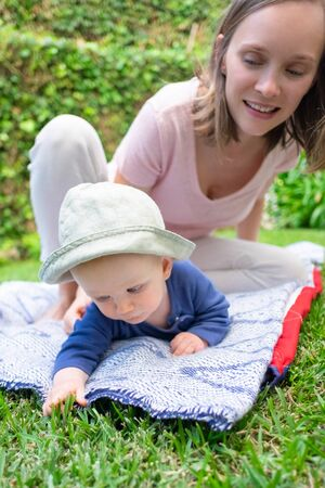Cute baby girl in blue shirt lying on belly in garden and touching grass. Beautiful mom watching daughter in park and smiling. Summer family time and sunny days concept