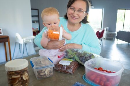 Grandmother with cute red-haired baby choosing food in container. Portrait of senior woman sitting at table, holding grandchild and looking at camera. Meal preparation and easy cooking concept
