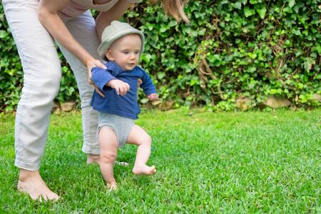 Lovely baby girl in hat and blue shirt doing first steps with help of mother. Young pretty mom holding daughter on grass. First barefoot steps, garden and sunny days concept