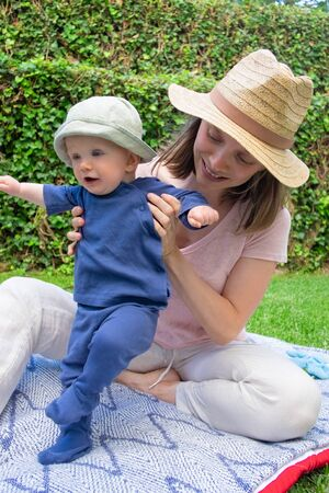 Little baby girl in blue clothes trying to walk on plaid. Young mom in hat holding her and smiling. Beautiful mother playing with daughter in garden. Sunny days and first steps concept