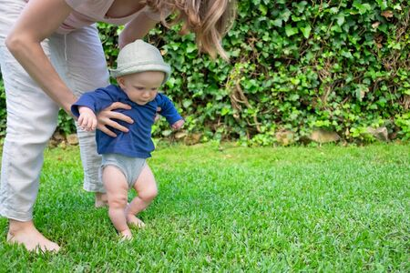 Adorable baby girl in hat and blue shirt doing first steps with help of mother. Young mom holding daughter on grass. First barefoot steps, garden and sunny days concept