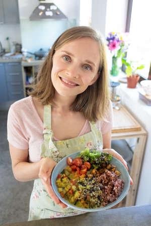 Joyful food blogger presenting homemade vegetable dish, standing in kitchen, looking at camera and smiling. Vertical shot, high angle. Healthy eating concept 写真素材 - 150597350