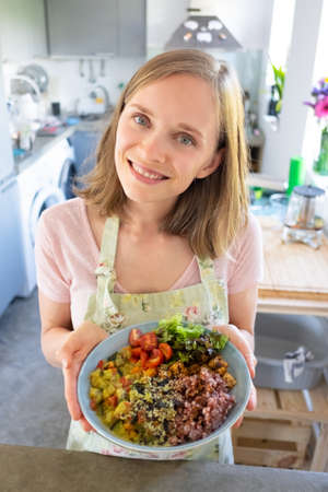 Positive happy young woman posing with homemade vegetable dish in her kitchen, showing bowl, looking at camera and smiling. Vertical shot, high angle. Healthy eating concept 写真素材 - 150597352