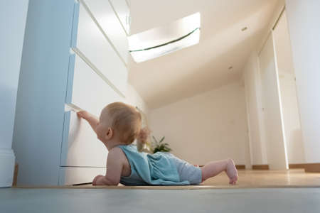 Adorable newborn opening closed wardrobe and lying on belly on wooden floor with barefoot. Side view of cute red-haired infant exploring room at home. Childhood and infancy concept Banque d'images