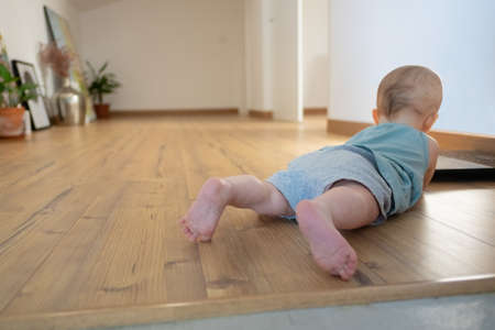 Little baby lying on belly on wooden floor with barefoot. Back view of adorable red-haired infant crawling at home. Childhood and infancy concept