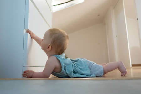 Lovely baby opening closed wardrobe and lying on belly on wooden floor with barefoot. Side closeup view of adorable red-haired infant exploring room at home. Childhood and infancy concept