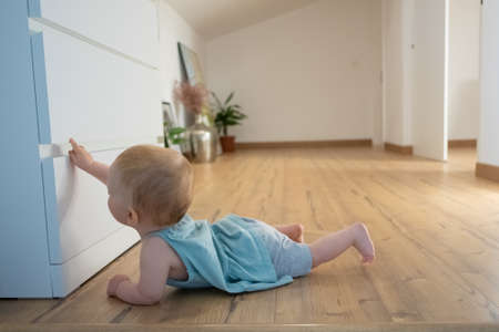 Cute newborn touching closed wardrobe and lying on belly on wooden floor with barefoot. Side view of adorable red-haired infant trying to crawl at home. Childhood and infancy concept Banque d'images
