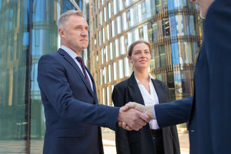 Confident businessmen shaking hands outdoors. Men and woman wearing office suits standing among city buildings and discussing contract. Agreement and partnership concept Archivio Fotografico