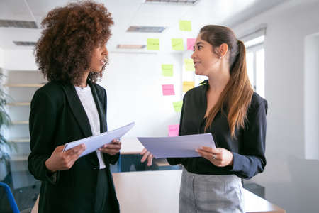 Pretty young businesswomen discussing project plan and smiling. Two beautiful female colleagues holding documents and talking in conference room. Teamwork, business and management concept