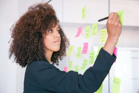 Beautiful young businesswoman writing on sticker with marker. Concentrated professional curly female manager sharing idea for project and making note. Brainstorming, business and management concept Banco de Imagens