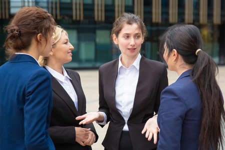 Creative female business team discussing project outdoors. Businesswomen wearing suits standing together in city and talking. Cooperation and teamwork concept