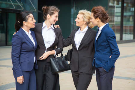 Happy businesswomen celebrating team success, standing outdoors, hugging and talking. Team support and congratulation concept Banco de Imagens