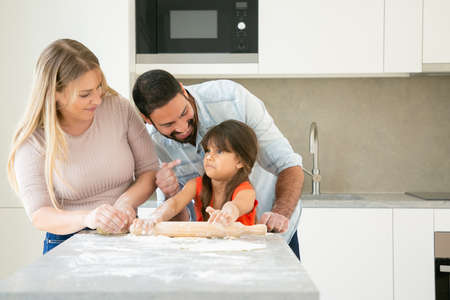 Joyful mom and dad staining girls face with flower while baking together. Young parents and daughter having fun while cooking in kitchen. Family home activity concept 写真素材