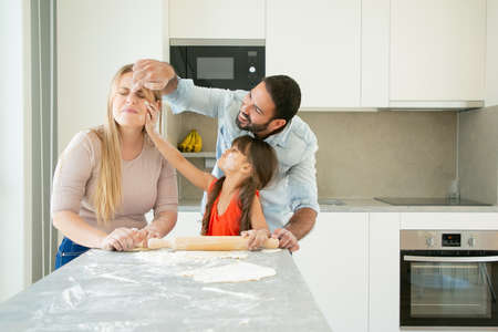 Happy positive mom, dad and girl staining faces with flower powder while baking together. Young parents and daughter having fun while cooking in kitchen. Family home activity concept 写真素材