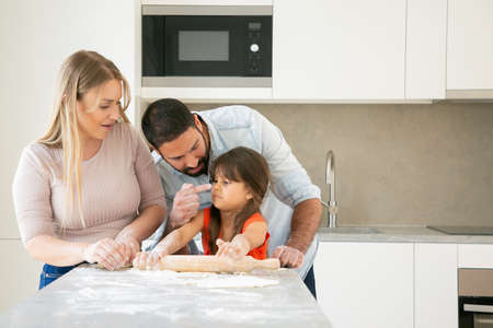 Happy mom and dad staining girls face with flower while baking together. Young parents and daughter having fun while cooking in kitchen. Family home activity concept