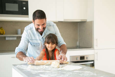 Cheerful Latin girl and her dad rolling and kneading dough on kitchen table with flour powder. Father helping daughter to bake bread or pies. Home activities concept