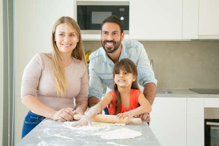 Cheerful mom, dad and girl with flower on faces enjoying baking together. Young parents and daughter having fun while cooking in kitchen. Family home activity concept