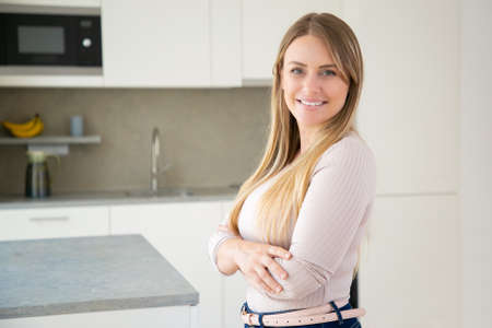 Cheerful attractive fair haired young woman posing with arms folded in kitchen, looking at camera and smiling. Medium shot, copy space. Woman at home or female portrait concept 版權商用圖片