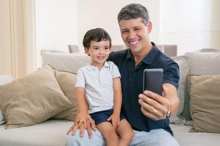Joyful dad and little son enjoying leisure time together