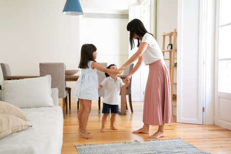 Young mom playing active game with happy children. Mother and kids dancing in round in apartment, having fun together, enjoying time at home. Family home activity or parenthood concept