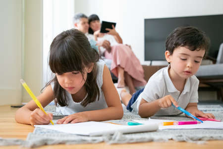 Focused little boy and girl lying on floor and drawing in living room while parents sitting together in background. Childhood or children creative development concept Foto de archivo