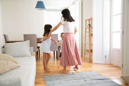 Mom playing active game with children. Mother and kids dancing in round, having fun together, enjoying time at home. Family home activity or parenthood concept