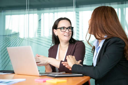 Excited cheerful businesswomen discussing project while sitting at open laptop, talking and smiling. Business communication and teamwork concept