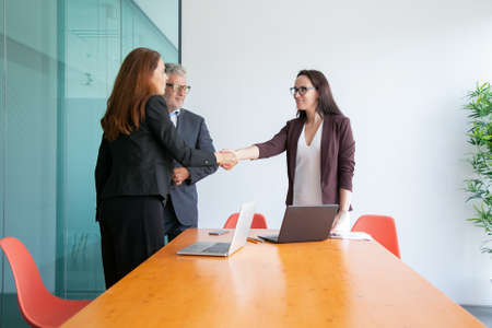 Successful businesswomen handshaking and greeting each other. Confident businessman in eyeglasses and middle-aged managers standing and meeting in conference room. Business and collaboration concept