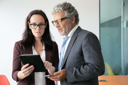 Brunette female assistant showing data to boss and holding tablet. Focused businessman looking on screen, holding phone and standing in conference room. Business and partnership concept