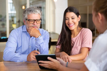 Happy young woman and mature man meeting with professional, watching and discussing content on tablet and laughing. Consulting or satisfied customers concept