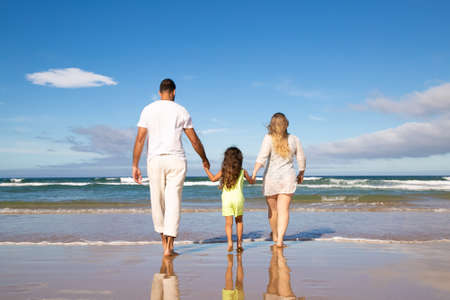 Man, woman and kid wearing pale summer clothes, walking on wet sand to sea, spending leisure time on beach. Rear view. Family outdoor activities concept