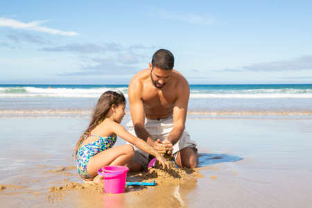 Adorable little girl and her dad building sandcastle on beach, sitting on wet sand, enjoying vacation. Bright blue sea with waves and white foam in background. Family summer holidays concept Reklamní fotografie