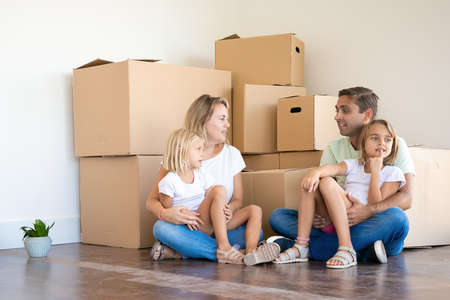 Happy Caucasian family sitting on floor with children. Mother, father and two daughters surrounded with cardboard boxes in new house or apartment. Mortgage, relocation and moving day concept